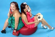 Due giovani donne che rivolgono ai telefoni su fondo blu Immagine Stock