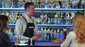 Due giovani donne che si siedono alla barra, parlante con un barista, il secondo barista sta venendo stock footage