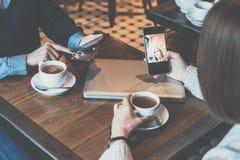 Due giovani donne che si siedono alla tavola in caffè e che per mezzo degli smartphones Ragazze che comperano online Immagini Stock Libere da Diritti