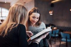 Due giovani donne che si siedono nel caffè bevente del caffè e che godono in buoni libri Studenti sulla pausa caffè Istruzione Immagini Stock