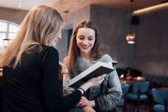 Due giovani donne che si siedono nel caffè bevente del caffè e che godono in buoni libri Studenti sulla pausa caffè Istruzione Fotografia Stock Libera da Diritti