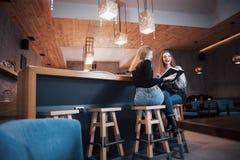Due giovani donne che si siedono nel caffè bevente del caffè e che godono in buoni libri Studenti sulla pausa caffè Istruzione Immagine Stock
