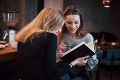 Due giovani donne che si siedono nel caffè bevente del caffè e che godono in buoni libri Studenti sulla pausa caffè Istruzione Fotografia Stock