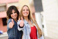 Due giovani donne con i pollici su all'aperto Immagine Stock