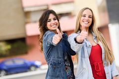 Due giovani donne con i pollici su all'aperto Immagine Stock Libera da Diritti