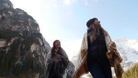 Due giovani donne coperte nelle coperte che camminano sulla costa del lago congelato stock footage
