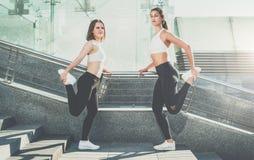 Due giovani donne, corridori delle ragazze stanno facendo allungando gli esercizi prima dell'correre Allenamento, addestramento,  Immagine Stock