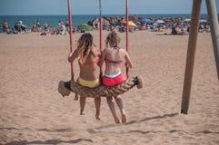Due giovani donne in costume da bagno su un'oscillazione sulla spiaggia Immagini Stock Libere da Diritti