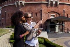 Due giovani donne di affari attraenti hanno conversazione fuori Le donne una è afroamericane Fotografie Stock Libere da Diritti