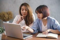 Due giovani donne di affari che si siedono alla tavola in caffè Donne asiatiche che per mezzo del computer portatile e della tazz Fotografia Stock