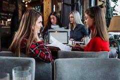 Due giovani donne di affari discutono il lavoro in un caffè Fotografie Stock Libere da Diritti