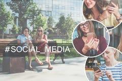 Due giovani donne di risata in vestiti che si siedono su un banco di parco, resto dopo la compera e per mezzo dei loro smartphone Fotografia Stock Libera da Diritti
