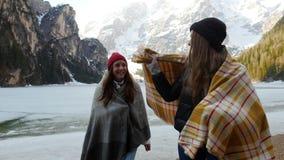 Due giovani donne di viaggio coperte nelle coperte che camminano vicino al lago congelato archivi video