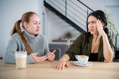 Due giovani donne discutono in caffè Discorso emozionale fotografia stock libera da diritti