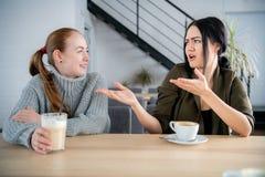 Due giovani donne discutono in caffè mentre bevono il caffè immagini stock