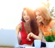 Due giovani donne discutono il video con il computer portatile che si siede ad un coffe Fotografia Stock Libera da Diritti
