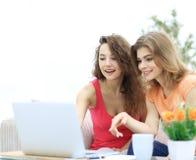 Due giovani donne discutono il video con il computer portatile che si siede ad un tavolino da salotto Immagine Stock Libera da Diritti