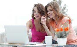 Due giovani donne discutono il video con il computer portatile che si siede ad un tavolino da salotto Immagine Stock