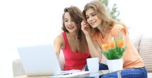 Due giovani donne discutono il video con il computer portatile che si siede ad un tavolino da salotto Fotografia Stock