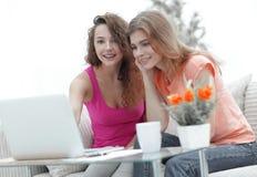 Due giovani donne discutono il video con il computer portatile che si siede ad un tavolino da salotto Immagini Stock Libere da Diritti
