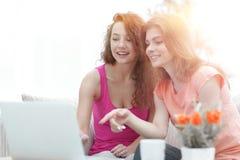 Due giovani donne discutono il video con il computer portatile che si siede ad un tavolino da salotto Fotografia Stock Libera da Diritti