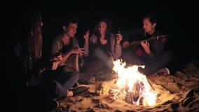 Due giovani donne e due uomini che si siedono tardi dal falò alle canzoni di canto e di notte, giocando chitarra e percussione stock footage