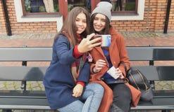 Due giovani donne fanno il selfie che si siede su un banco Fotografia Stock