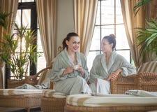 Due giovani donne felici che bevono tè alla località di soggiorno di stazione termale Fotografia Stock Libera da Diritti
