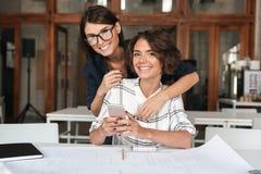 Due giovani donne felici che per mezzo dello smartphone dalla tavola Fotografie Stock