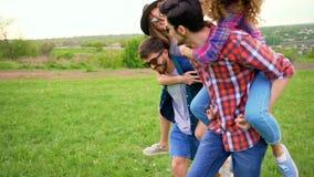 Due giovani donne felici stanno guidando due uomini alla moda nel parco stock footage