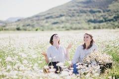 Due giovani donne graziose che hanno picnic con tè nel campo della camomilla Immagini Stock