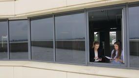 Due giovani donne hanno camminato più alla finestra aperta in ufficio e nella conversazione archivi video