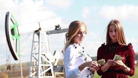 Due giovani donne hanno convertito i dollari in giacimenti di petrolio Reddito da olio video d archivio