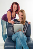 Due giovani donne in jeans che rimandano una compressa Immagine Stock