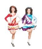 Due giovani donne nel dancing del vestito da ballo dell'Irlandese isolate Fotografia Stock