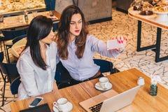Due giovani donne si siedono in un caffè ad una tavola davanti ad un computer portatile e fanno il selfie su uno smartphone Riuni Fotografie Stock