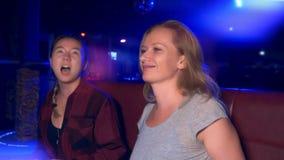 Due giovani donne sorridenti asiatiche e caucasiche ad una tavola in un night-club stock footage