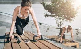 Due giovani donne sorridenti, ragazze in abiti sportivi che fanno gli esercizi mentre ascoltando la musica Allenamento, coricante Immagine Stock