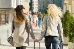 Due giovani donne stanno camminando lungo una via della città, il giorno soleggiato di autunno, l'ora dorata, vista dalla parte p fotografia stock