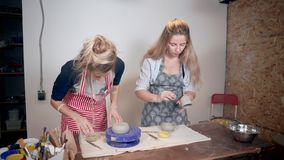 Due giovani donne stanno lavorando in terraglie, facenti le stoviglie dell'argilla stock footage
