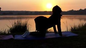 Due giovani donne stanno a quattro zampe e preparano la respirazione sulla Banca del lago al tramonto stock footage