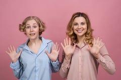 Due giovani donne, studenti sorridono felicemente e mostrano le palme aperte loro che esprimono la gioia e la disattenzione immagini stock libere da diritti