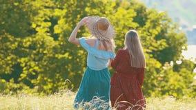Due giovani donne sul campo di estate Uno di loro sta filando e ridendo video d archivio