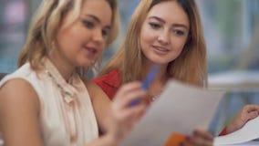 Due giovani employeers discutono le nuove idee circa lo sviluppo della loro società facendo uso delle carte, degli autoadesivi e  archivi video