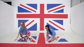 Due giovani femmine sorridenti attivamente stanno ballando sul fondo della bandiera di britannici stock footage