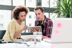 Due giovani impiegati che guardano un video sul PC della compressa nell'ufficio Immagine Stock