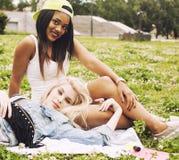 Due giovani migliori amici graziosi delle ragazze dell'adolescente che mettono su erba che fa la foto del selfie divertendosi, ge Immagine Stock
