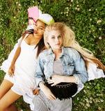 Due giovani migliori amici graziosi delle ragazze dell'adolescente che mettono su erba che fa la foto del selfie divertendosi, ge Fotografia Stock Libera da Diritti