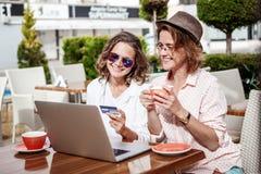 Due giovani ragazze attraenti delle amiche delle donne stanno sedendo in un Ca immagini stock