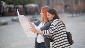 Due giovani ragazze attraenti stanno guardando da parte nella zona urbana mentre esploravano la città Le donne caucasiche stanno  stock footage